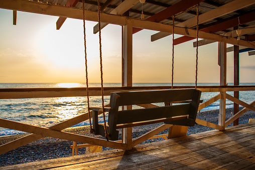 Swing bench on the beach by the sea against the backdrop of sunset