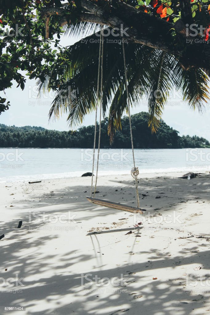 Swing on the beach under the palm trees stock photo