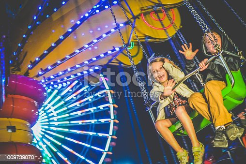 Two cute kids on a carnival ride, a big swing, in the evening, enjoying themselves at the fair