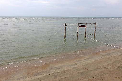 View from the beach of a large wooden rope swing installed in the ocean shallows for tourists to use, southeast Asia