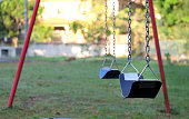 istock Swing set at a playground that is empty. Warm morning sunlight. 1259387134