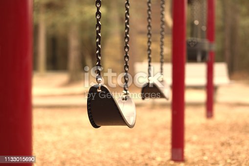 Swings hanging on empty school or park playground.  Bench and trees in background.  No people.  Loneliness, child abuse, childhood, education concepts.
