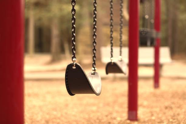 Swing set on empty school or park playground. stock photo