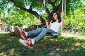 Young caucasian beautiful woman swinging in shade under a tree and using her phone.