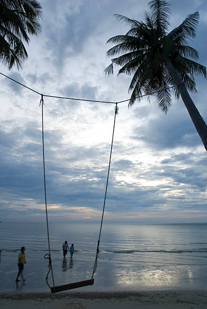 Swinging at twilightat sunset on the beach A simple swing stands along the beach with the sun setting in front.Some sea and beach pictures below: koh chang stock pictures, royalty-free photos & images