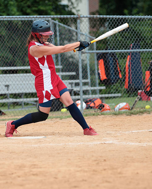 swinging batter - softball stock photos and pictures