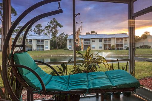Schwingende Loungesessel Auf Einer Terrasse Bei Sonnenuntergang Als Es Mit Blick Auf Einen Teich Stockfoto Und Mehr Bilder Von Abenddammerung Istock
