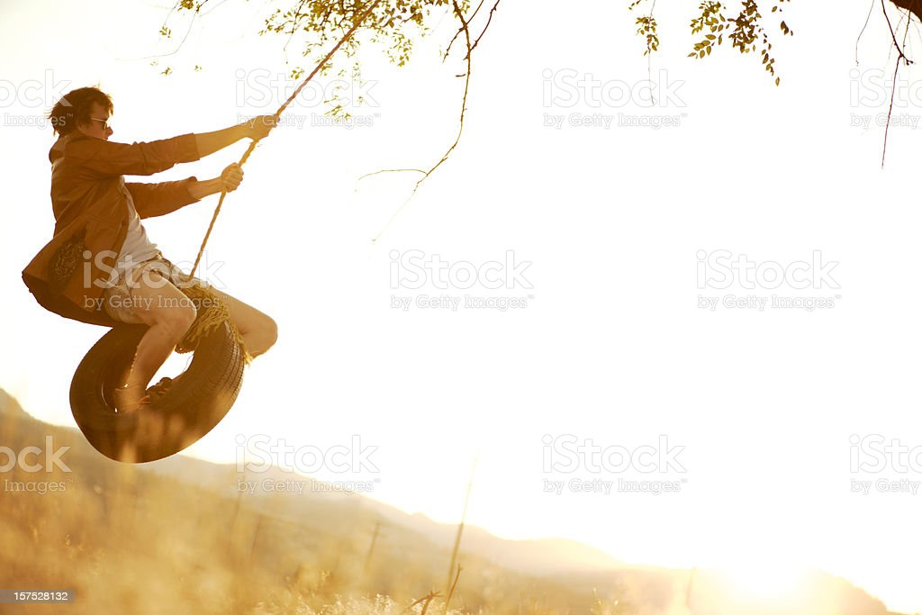 Swinging on a rope swing at sunset royalty-free stock photo