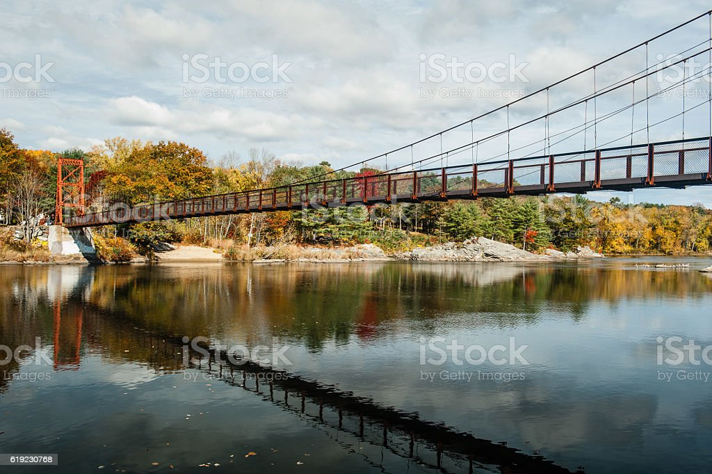 Swinging pedestrian bridge over the Androscoggin River in Brunswick, Maine stock photo