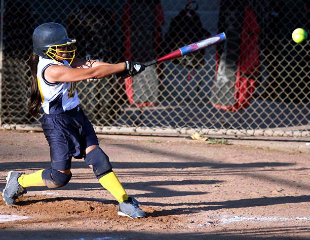 swinging with power - softball stock photos and pictures