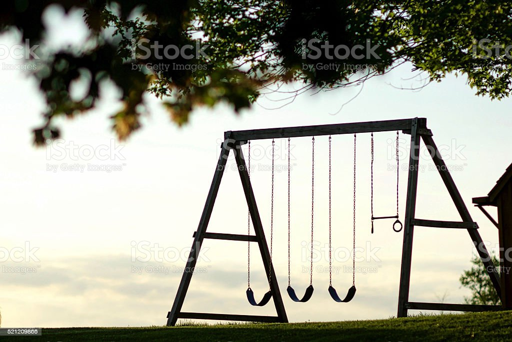 Swingset at sunset, silhouette stock photo