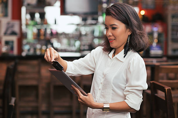Swiping card payment Bar owner using credit card reader on the tablet to swipe payment smart card stock pictures, royalty-free photos & images