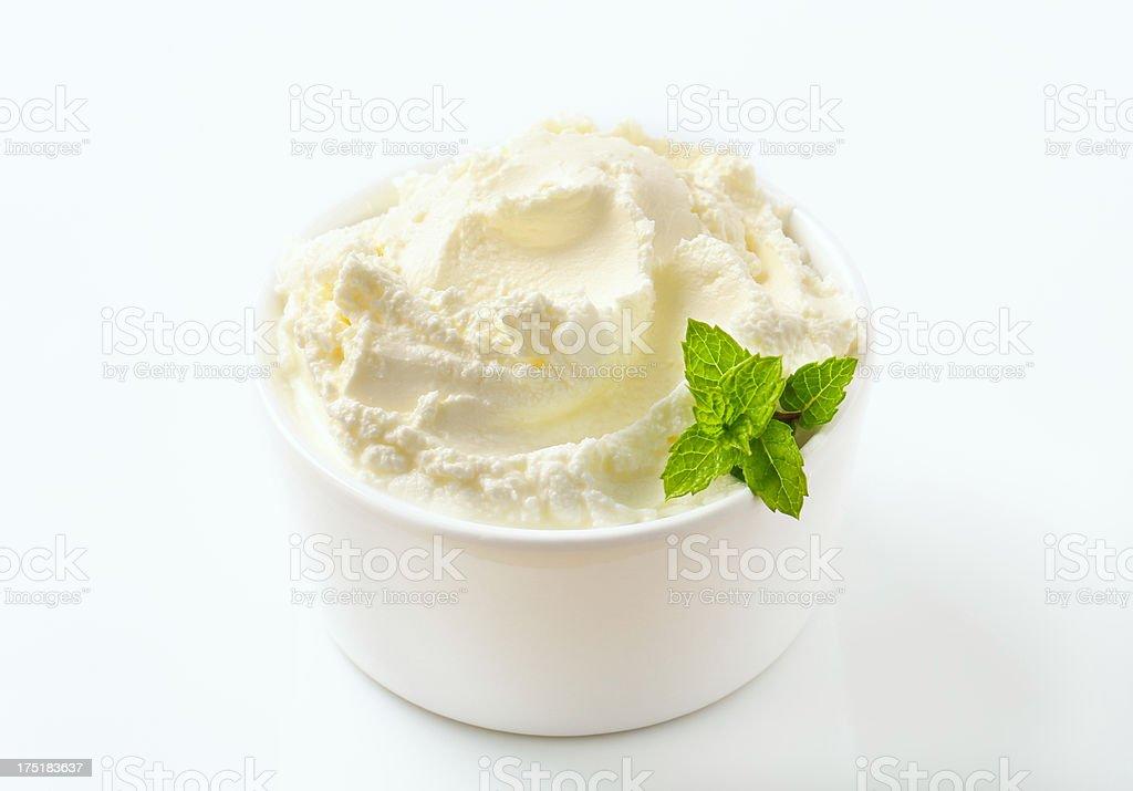 Swirl smooth sweet cream cheese in ramekin with mint leaves stock photo