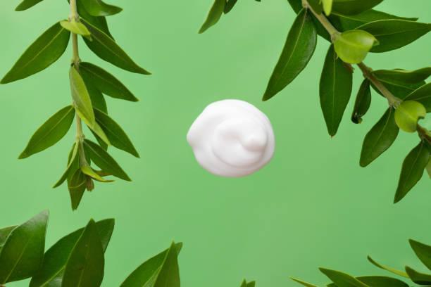 Wirbeln seidig weiß Dollop von Gesicht Creme Körperlotion auf grünem Hintergrund mit frischen Pflanzen Blätter. Hautpflege Schönheit Bio Kosmetik Wellness-Konzept – Foto