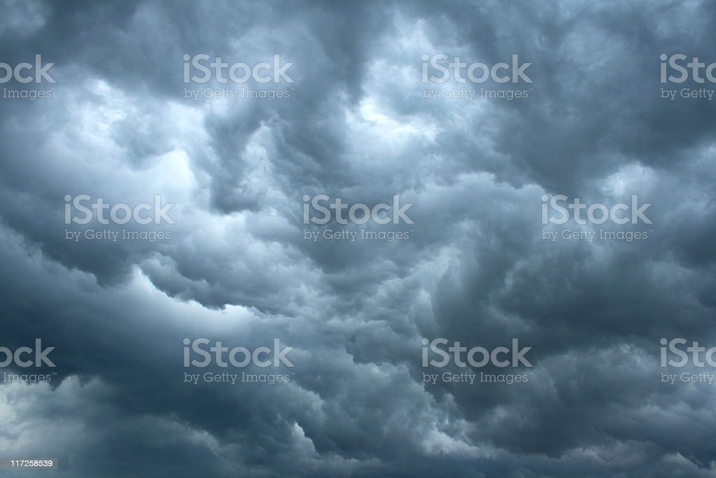 Swirling, threatening gray storm clouds filling sky stock photo