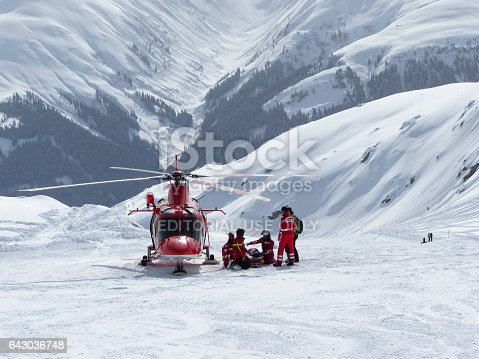 Disentis/Muster, Switzerland - 18 February 2014: Next to a landed Agusta A109SP rescue helicopter of Swiss Air-Rescue association