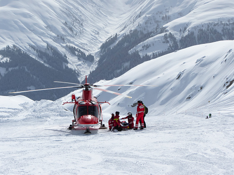 Swiss air rescue helicopter next to injured skier on ski piste