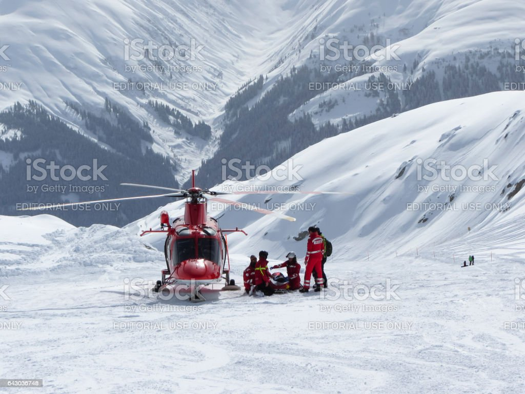 Swiss air rescue helicopter next to injured skier on ski piste stock photo