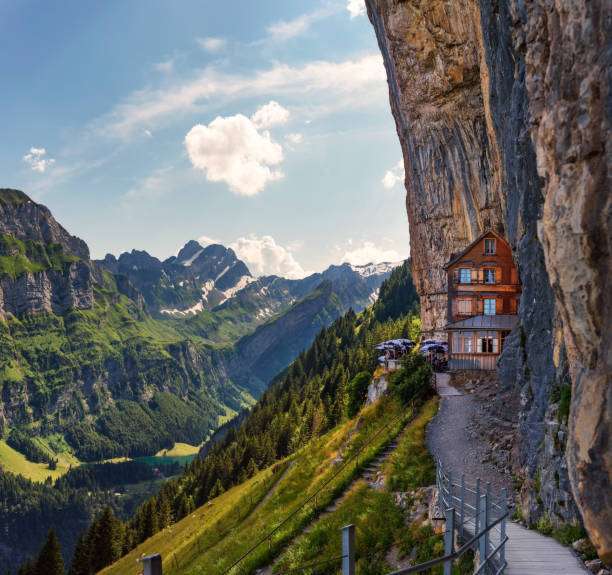 Swiss Alps and a restaurant under a cliff on mountain Ebenalp in Switzerland stock photo