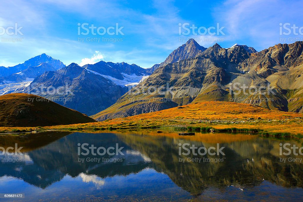 Swiss alps landscape: Alpine Lake reflection, golden meadows above Zermatt stock photo