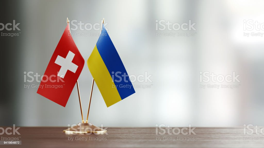 Swiss And Ukrainian Flag Pair On A Desk Over Defocused Background stock photo
