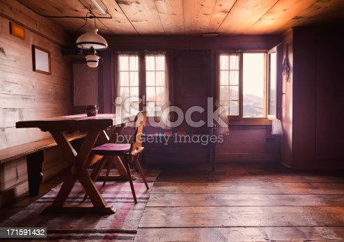 Swiss cabin dining room interior back lit by open windows. Focus on the table and chair. Some smoke from a nearby fire diffusing the light. One of the windows is open.
