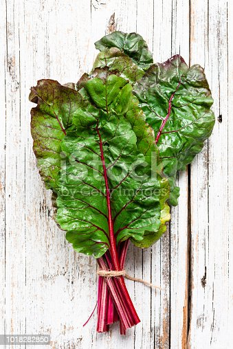 Swiss chard leaf on white wooden background. Top view. Organic green healthy food
