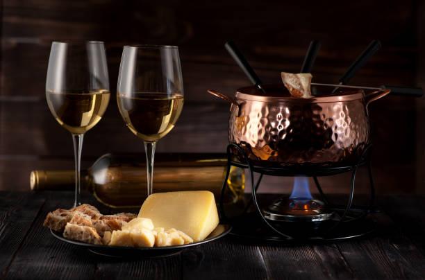 schweizer käsefondue auf rustikalen hintergrund - fondue zutaten stock-fotos und bilder