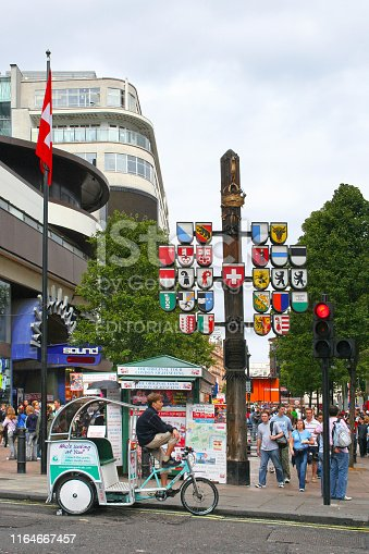 London, England - August 19 2006: People walking through Swiss Court, part of Leicester Square in Central London. Leicester Square is at the heart of London's entertainment district, with several cinemas and other places of interest. At the entrance of the court, there is a wooden post displaying with the 26 coat of arms of the Swiss Confederation.