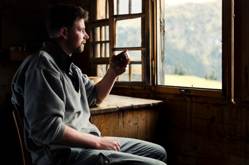 Swiss farmer with his morning coffee watching Alps