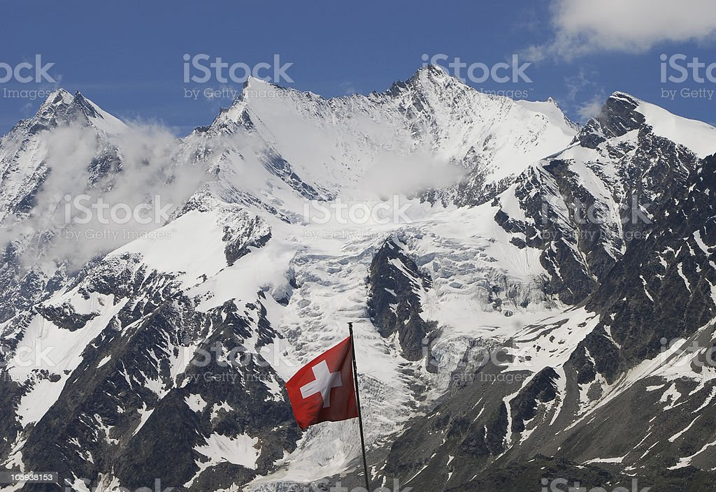 Swiss Flag against Mountains in the Valais Canton royalty-free stock photo
