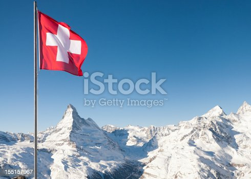 The white cross on red background of the Swiss national flag flying high above the Alps, with the Matterhorn directly underneath the flag.  Taken at the ski resort of Zermatt.