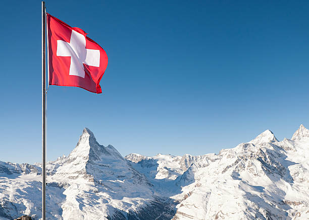 Swiss Flag and the Matterhorn The white cross on red background of the Swiss national flag flying high above the Alps, with the Matterhorn directly underneath the flag.  Taken at the ski resort of Zermatt. switzerland stock pictures, royalty-free photos & images