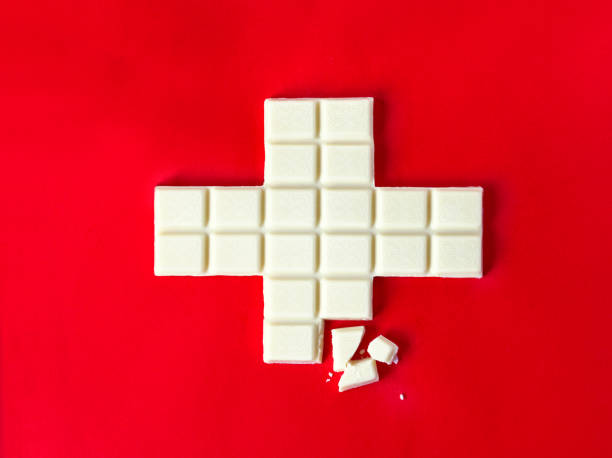 Swiss flag cross in form of white chocolate with some pieces over the red background Swiss flag cross in form of white chocolate with some pieces over the red background swiss culture stock pictures, royalty-free photos & images