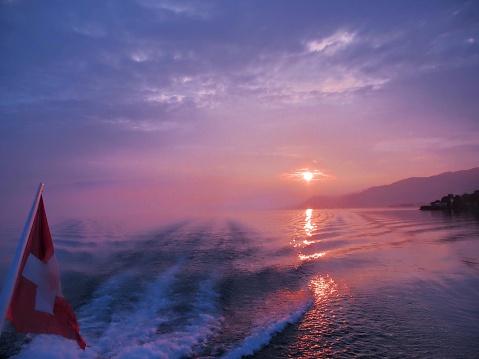 Swiss flag during sunset on Lake Geneva