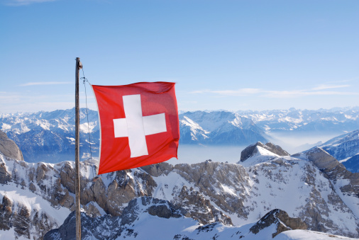Swiss flag flying over snowy mountains