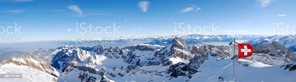 swiss flag in the wind over panoramic mountain view (XXL) stock photo