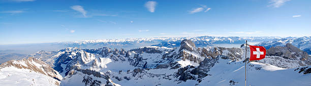 swiss flag in the wind over panoramic mountain view (XXL)  swiss alps stock pictures, royalty-free photos & images