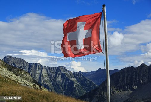 Swiss flag waving in the wind in the mountains of Ticino, Switzerland.