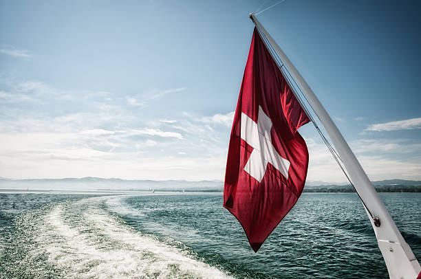 Swiss flag waving in the wind during a sailing boat trip on the Lake Constance in Switzerland, the lens flares are intended and added in afterprocess Bodensee stock pictures, royalty-free photos & images