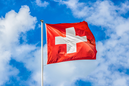 Swiss flag waving in the wind on a sunny day with blue sky and clouds