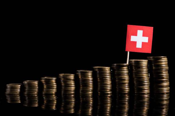 Schweizer Flagge mit Menge von Münzen auf schwarzem Hintergrund isoliert – Foto