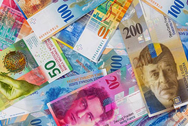 swiss franc banknotes as background - franken stockfoto's en -beelden