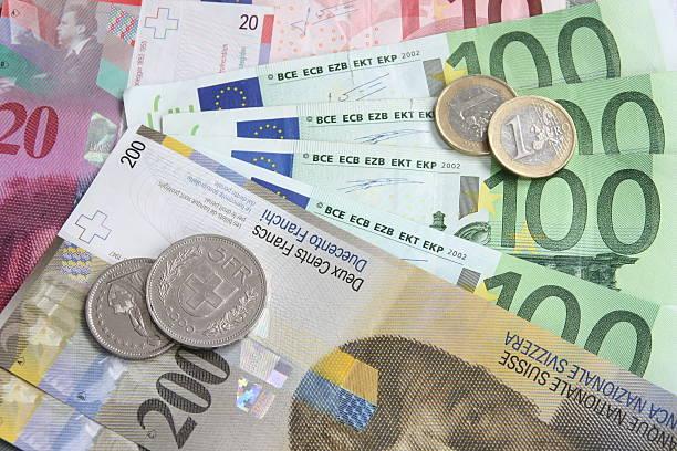 swiss franc versus euro - franken stockfoto's en -beelden