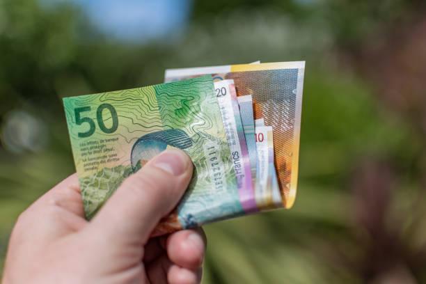 zwitserse franken (chf) papier valuta buiten - franken stockfoto's en -beelden