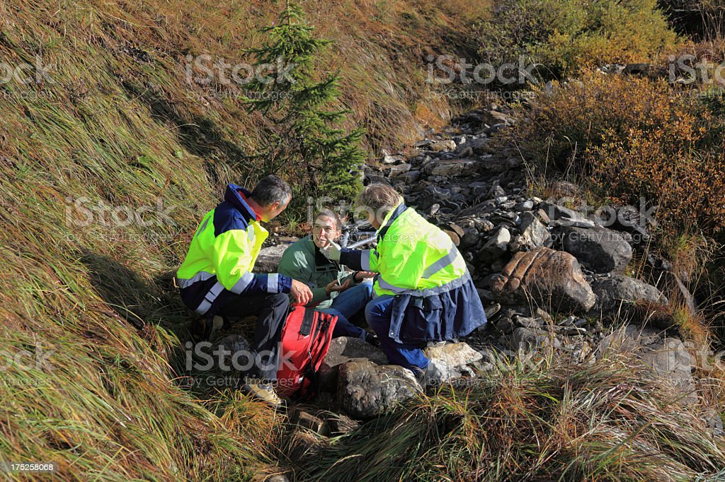 swiss mountain rescue team help injured girl in alps royalty-free stock photo