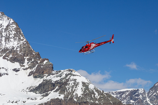 Zermatt, Switzerland - April 13, 2017: A red rescue helicopter flying in the Matterhorn Area in the Swiss Alps