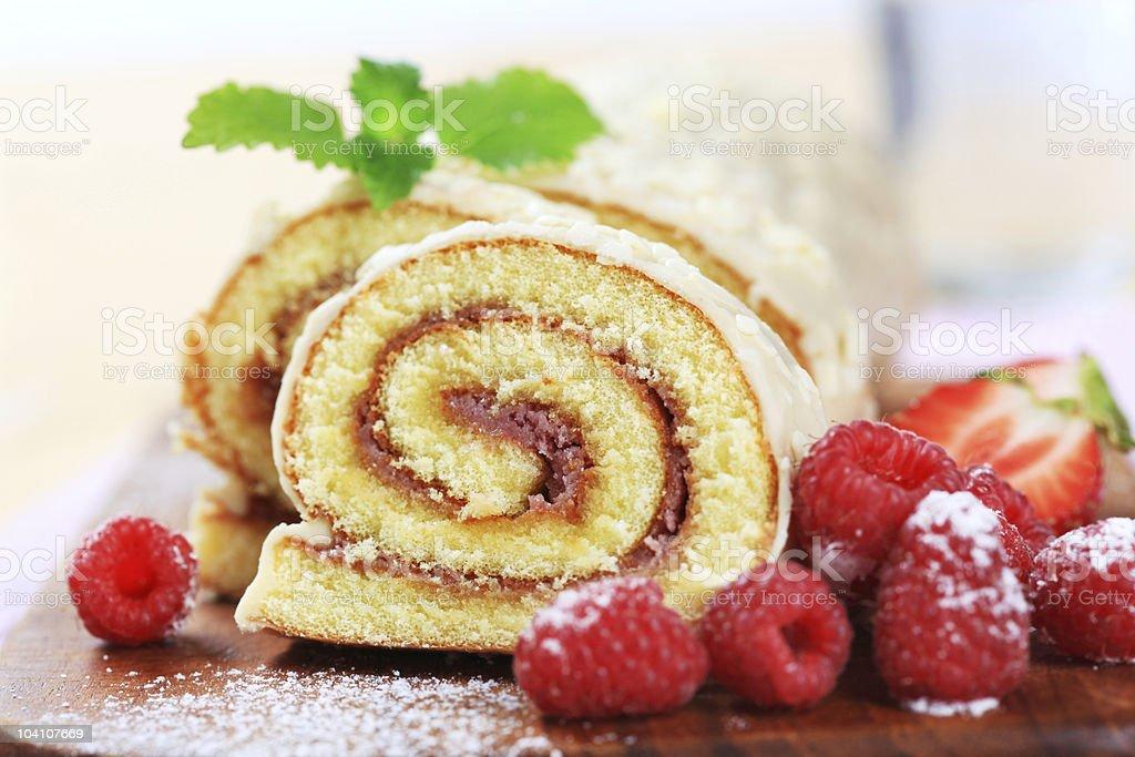 Swiss roll dessert cut in half with berries stock photo