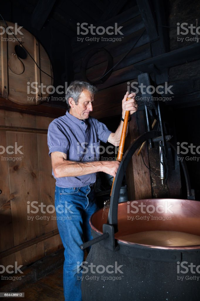Swiss sheep farmer makes cheese in traditional way in smokey Swiss mountain chalet stock photo