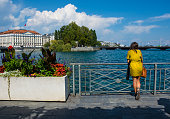 Geneva, Switzerland - August 29, 2019. Girl looking at the view on the promenade, the shore of the Leman lake in Geneva city, Switzerland.